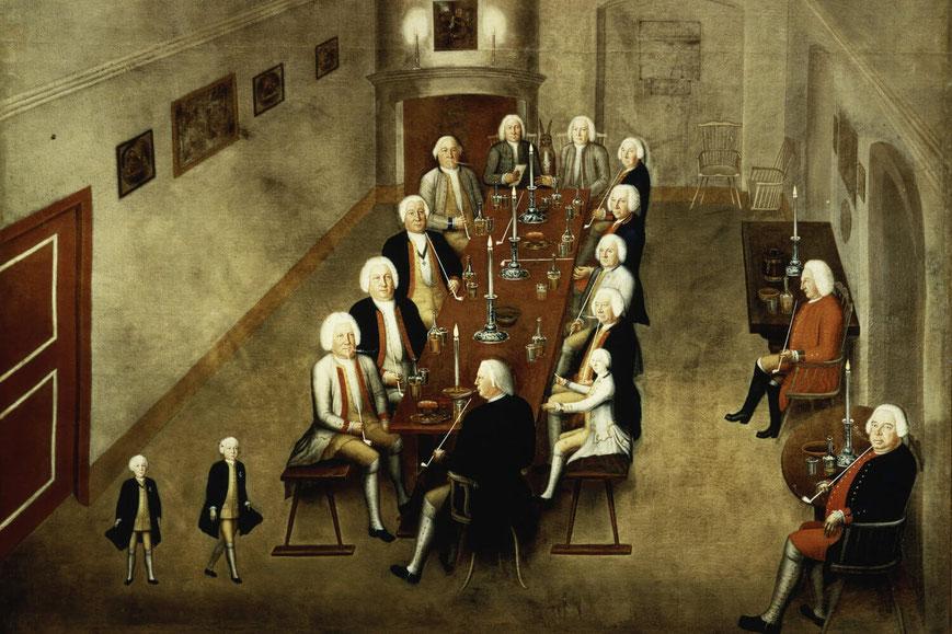 An einem langen Tisch in einem kargen Raum sitzend rauchen Männer mit weißen Perücken Pfeife.