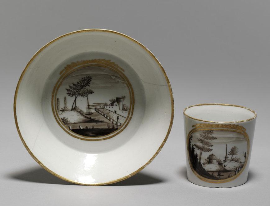 Kaffeetasse mit Untertasse. Die Untertasse ist als Schale ausgearbeitet. Das Dekor besteht aus einer Hafenszene.