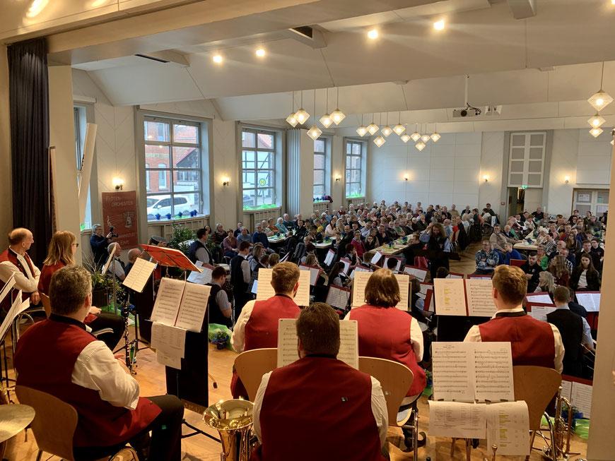 Stephan Pfannkuchen dirigiert das Flötenorchester, während die Musiker des Posaunenchores Deinsen sich auf der Bühne sitzend eine Pause gönnen. Das gemeinsame Konzert ist sehr gut besucht.