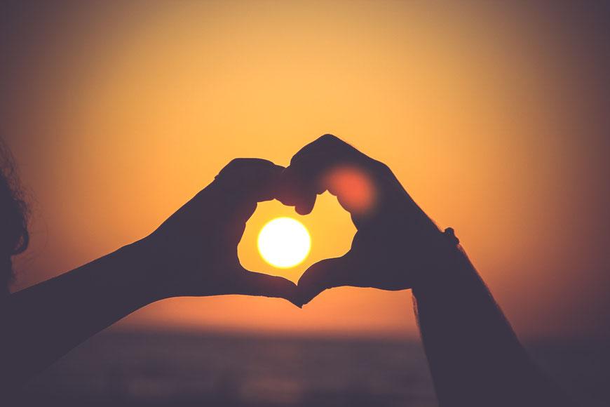 Zwei als Herz geformte Hände mit untergehender Sonne in der Mitte
