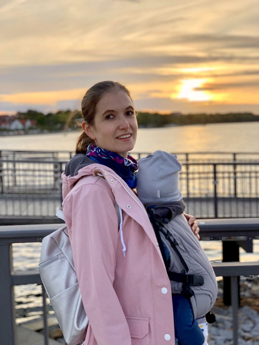 Mama und Sohn mit der Babytrage im Urlaub unterwegs. Erster Urlaub mit Baby am Meer beim Sonnenuntergang.