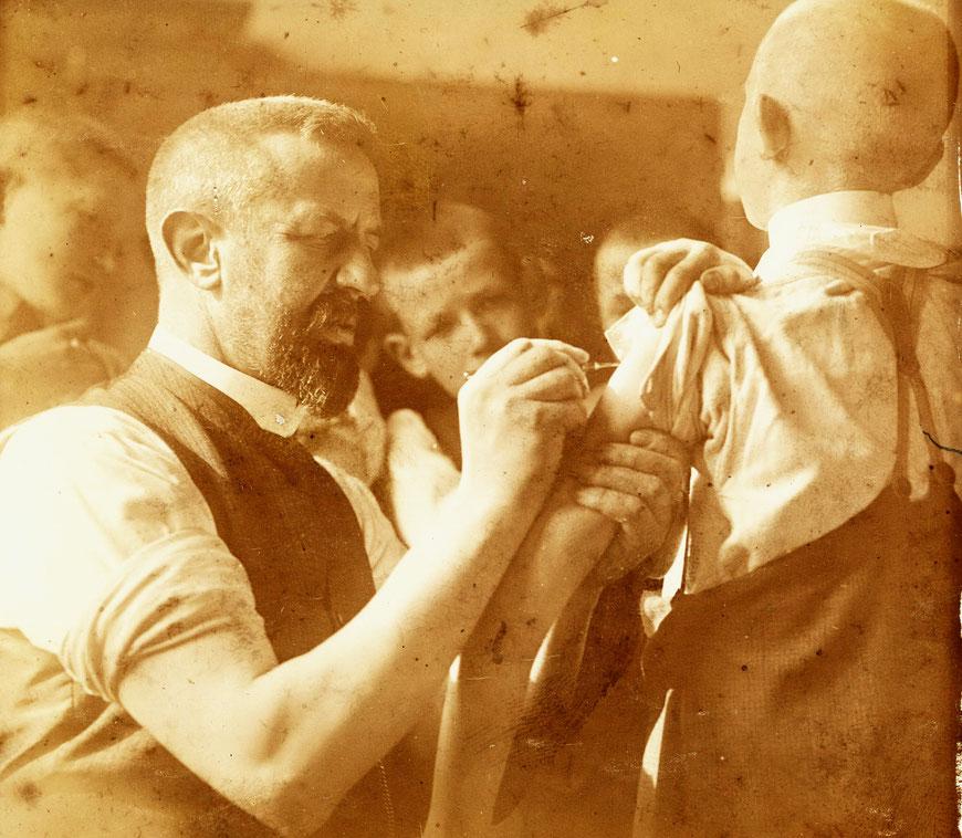 Vater Heinrich beim Impfenmit derr damals üblichen Lanzette