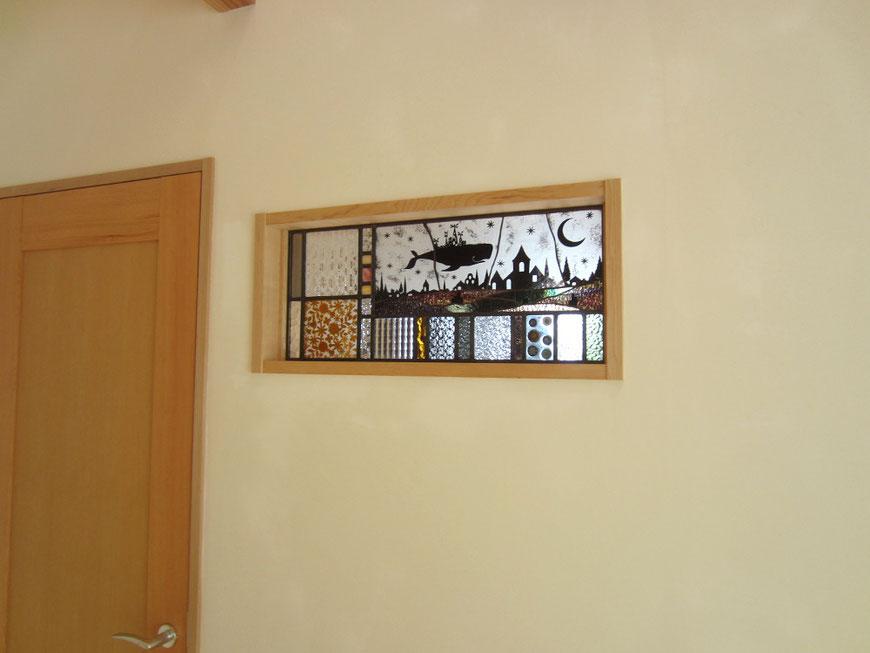 リビングと玄関ホールの壁に組込んだ、小さな姉妹の夢を描いたステンドガラスの絵
