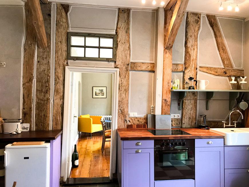 Die Küche der Ferienwohnung mit Blick in das Wohnzimmer. Im Fokus steht das alte Fachwerk.