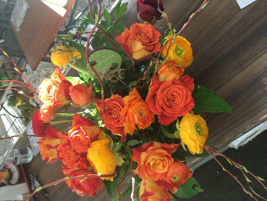 Blumenstrauß mit orangefarbenen Rosen und gelben Ranunkeln