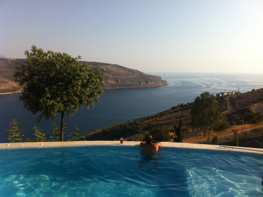 A kind gesture picture of one of our guests during his afternoon enjoying the pool, his drink and the scenery unfolding round the bay below him