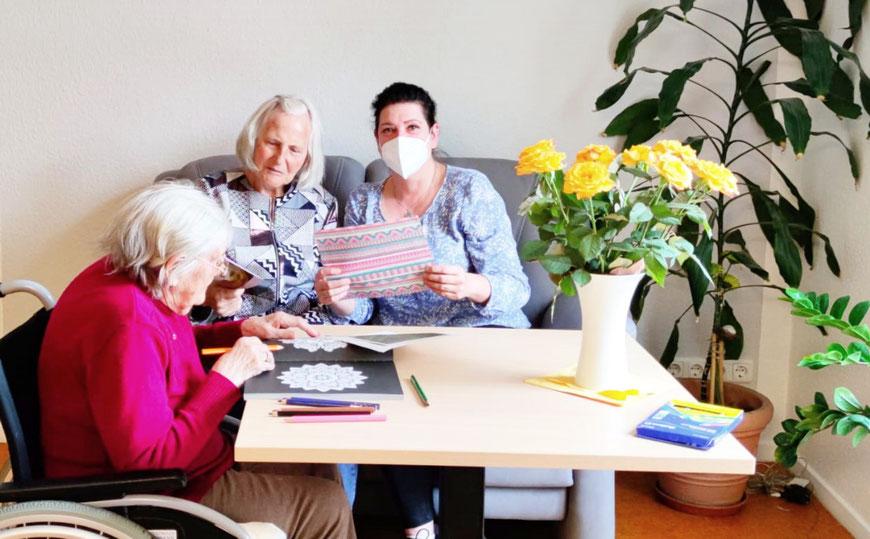 Pflegedienstleiterin Kathrin Gösch mit 2 Bewohnern in der neuen Sitzecke