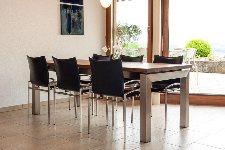 Tisch mit Nussbaum Platte und Edelstahl Fussgestell.