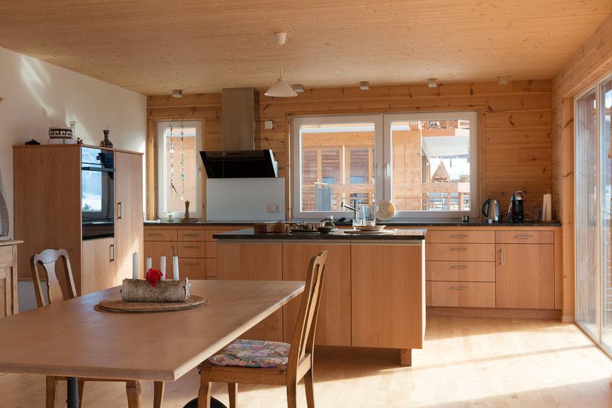 Offene Küche mit Insel. Fronten aus Buchenholz, Arbeitsplatte aus Naturstein und eine edle Abzugshaube aus Edelstahl.