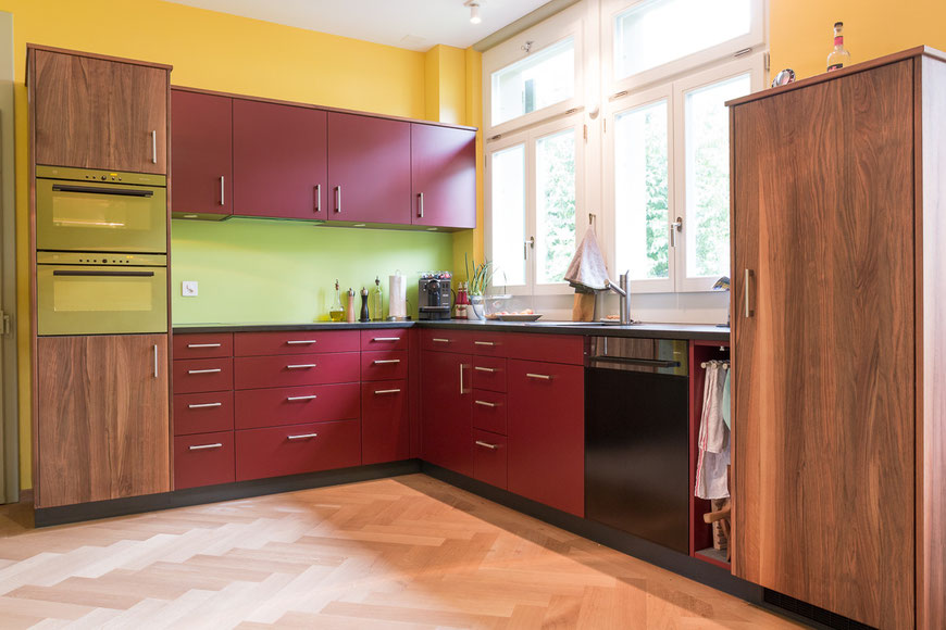 Küche aus Nussbaumholz kombiniert mit bordeaux farbig lackierten Fronten.