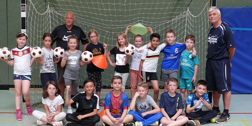 Die beiden professionellen Trainer der Fußballschule NRW kamen in einer der Pausen während des Spielablaufs zu einem kurzen Fotoshooting mit den Kindern zusammen. Foto: Sabine Rühmer