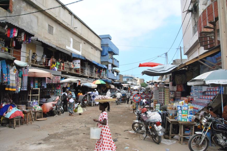 Vue d'une petite rue du marché où se mêlent magasins formels, stands sur les trottoirs et vendeurs ambulants.