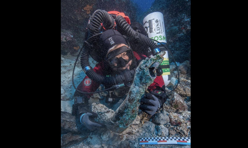 archaeologist recovering bronze arm from Antikythera shipwreck