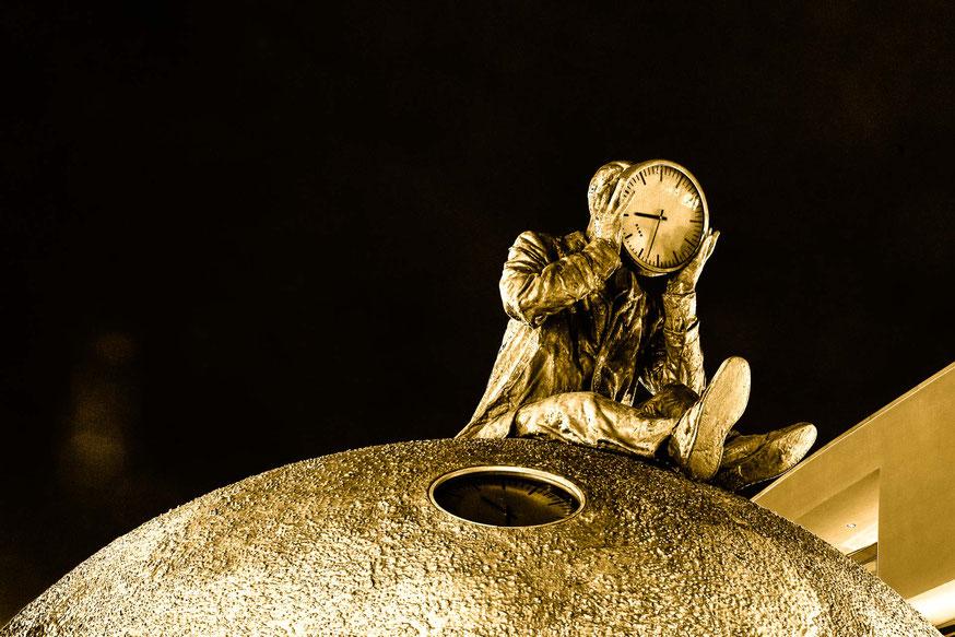Skulptur Mann mit Uhr in den Händen bei Nacht in Magdeburg