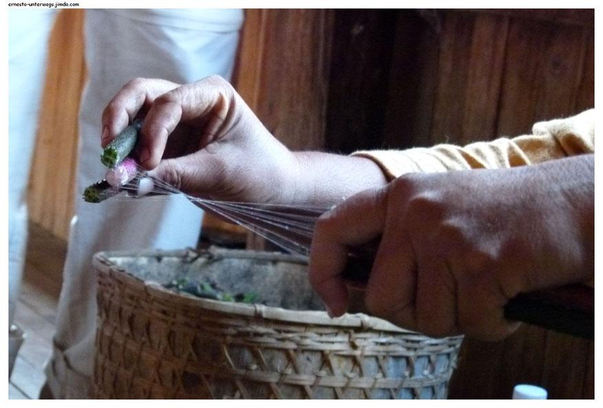 Hier wird Lotosseide gewonnen, indem man die Stiele der Lotosblume bricht und auseinanderzieht. So werden die innenliegenden Seidenfäden freigelegt.