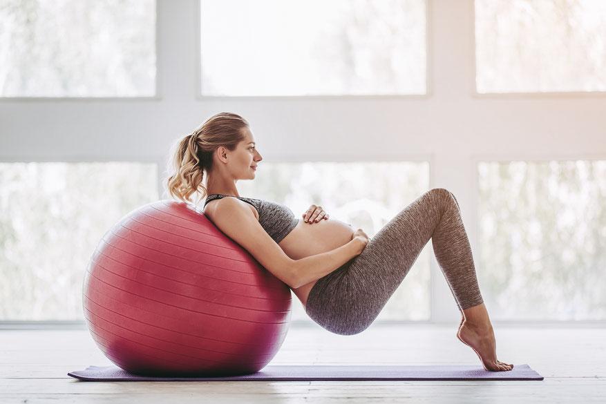 Schwangere in Sportkleidung lehnt auf Gymnastikball und umfasst ihren Bauch. Omega-3 in der Schwangerschaft: Dr. Marquardt berät zur richtigen Fett- und Nährstoffversorgung.