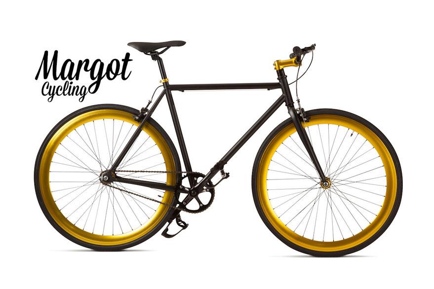 Fixed bike MARGOT ELDORADO. Telaio nero opaco e parti nere. Spicca il luminoso ORO anodizzato di cerchi, collarino, pipa manubrio e mozzi. Luminosità ed eleganza!