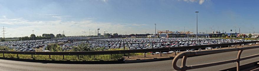 Auto-Lagerfläche auf dem Logport-Gelände. Bei sommerlichen Temperaturen ein einziger Hitzespeicher, dessen  hohe Temperaturen bei den vorherrschenden Westwinden in die Innenstadt verfrachtet werden.  Angereichert mit Auto- und Schiffsabgasen.