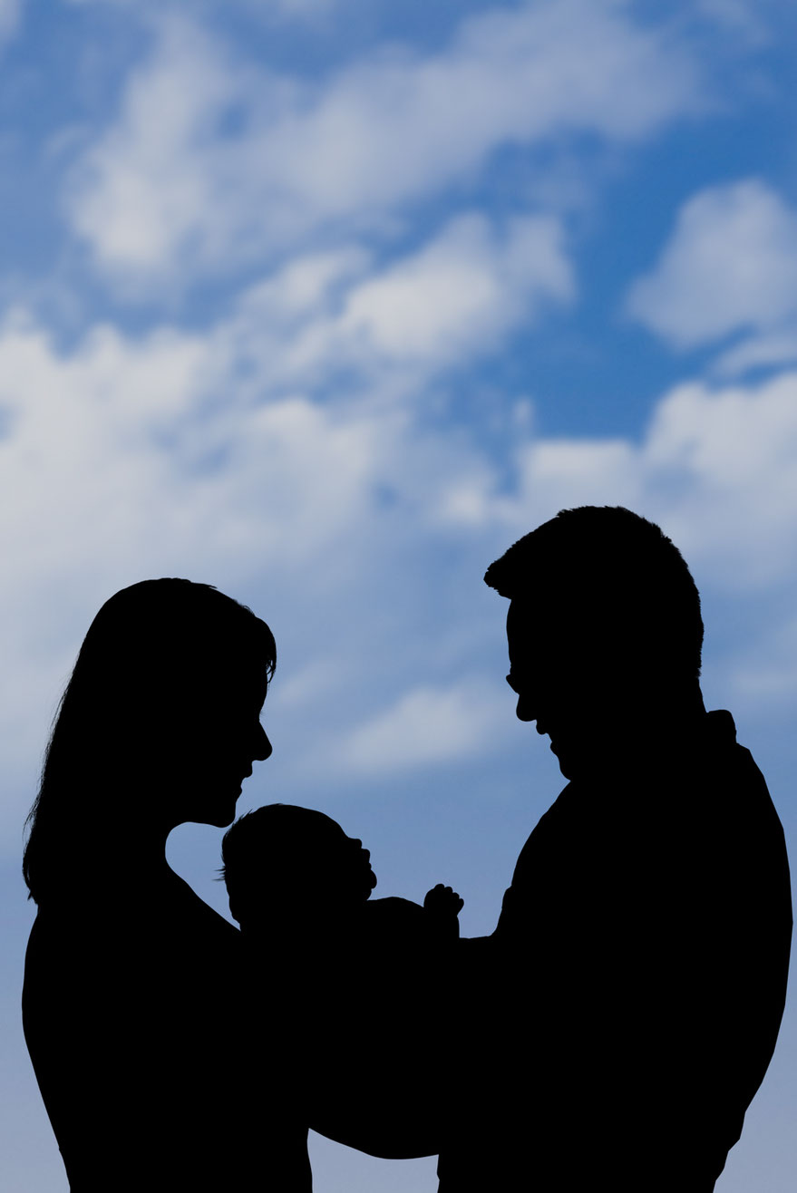 black and white silhouette of mother, new baby, and father against a blue sky with clouds