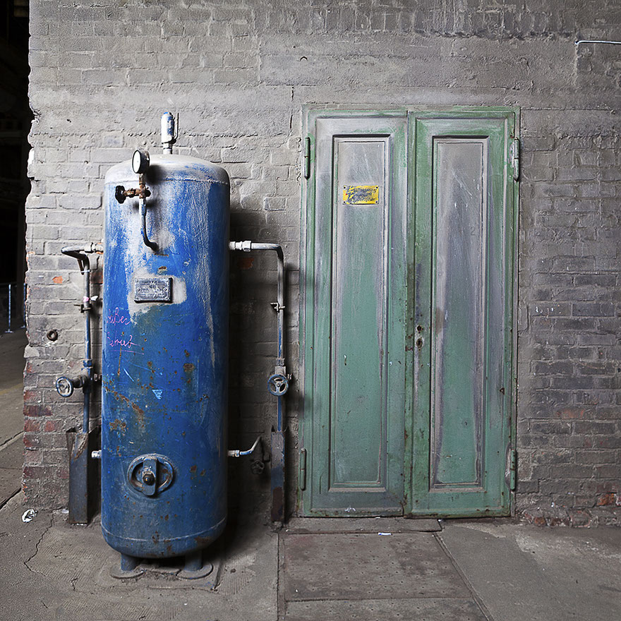 Blauer Behälter steht neben einer grünen Doppeltür in alter Fabrikhalle