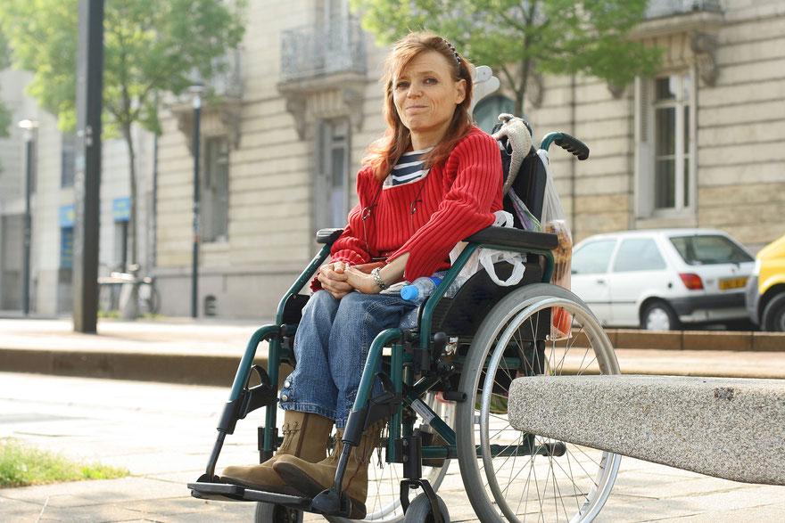 Frau im Rollstuhl, im Hintergrund eine Häuserfassade und parkende Autos © AdobeStock