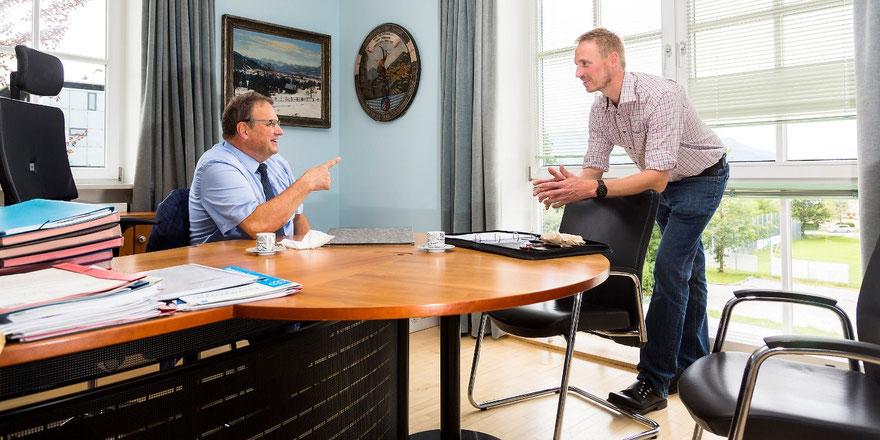 Stefan Klaffenbacher im Büro mit Landrat Josef Niedermier stehend auf eine Stuhllehne gestützt und
