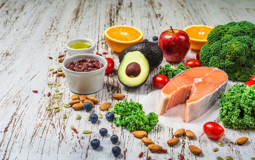 Lebensmittel auf dem Tisch ausgebreitet, die wichtig für Omega-Eating sind, weil sie ein gutes Fettsäure-Verhältnis haben und gesunde Nährstoffe liefern sind. Zum Beispiel: Bohnen, Avocado, Nüsse, frisches Obst und Gemüse.
