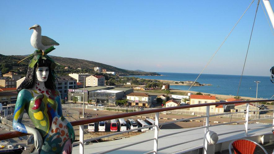 Blick vom Schiff auf die wartenden Ausflugsbusse und den Stadtstrand