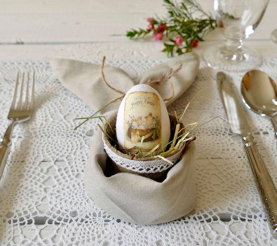 Gedeckter Tisch mit Osterei im Torftöpfchen und Serviette
