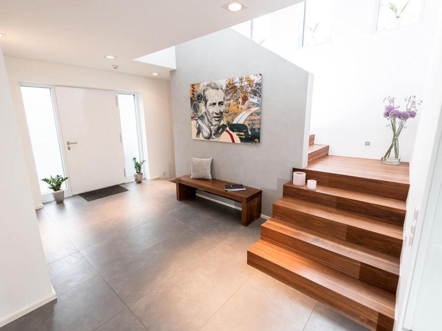 Heller, großzügiger Eingangsbereich eines modernen Wohnhauses mit Haustür und Treppe