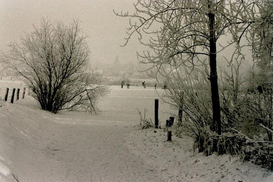 Ein stimmungsvolles Winterbild aus den 1980er Jahren zeigt Kinder auf dem zugefrorenen Wittrocksee mit der Kirchweyher Kirche im     Hintergrund. [Foto: H.Tödtmann]