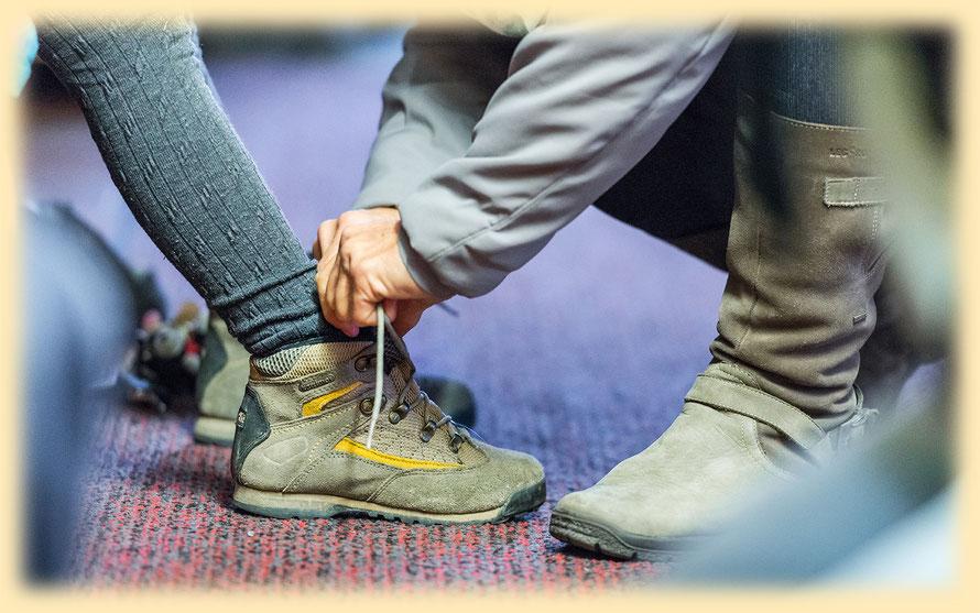 Mutter bindet dem Kind die Schuhe zu
