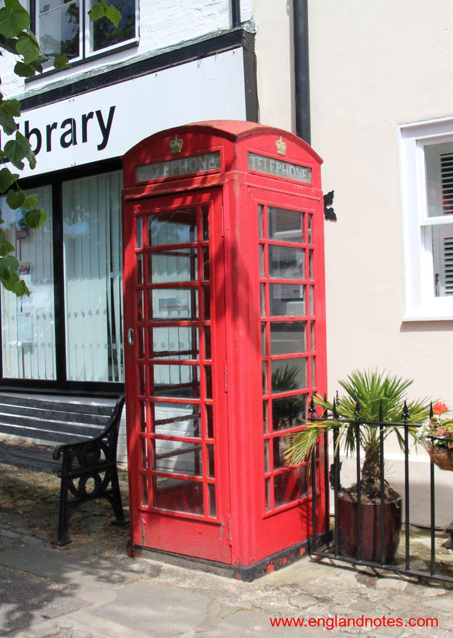 Rote englische Telefonzelle vor der Bibliothek in Lenham in Kent, England.