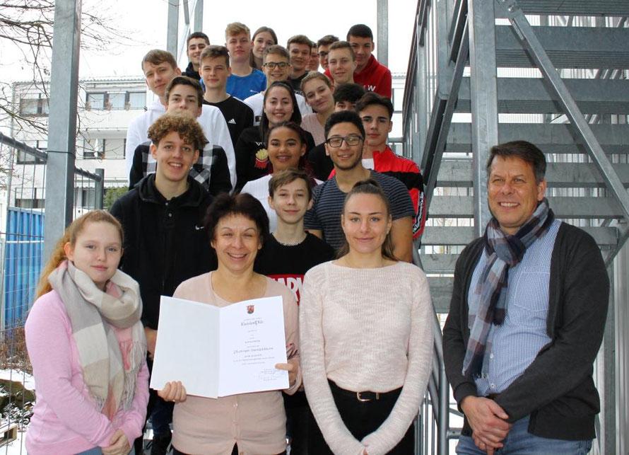 Frau Hänling im Kreise ihrer Schülerinnen und Schüler mit Schulleiter Herrn Engel