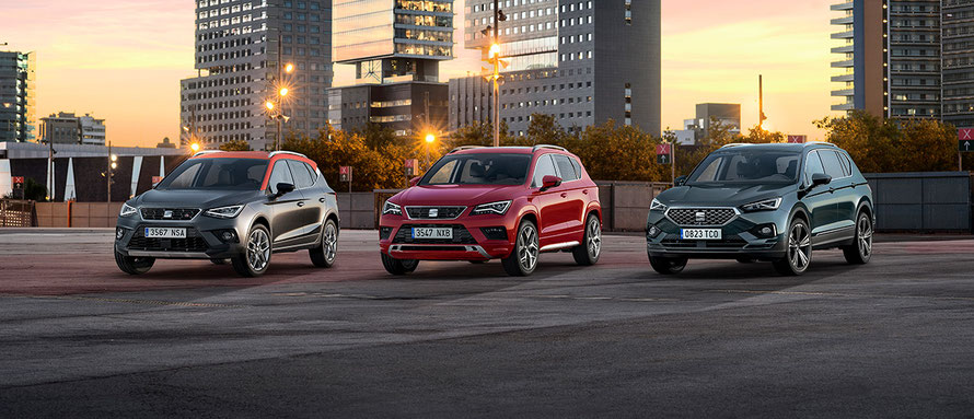 Drei SEAT Fahrzeugmodelle in verschiedenen Farben stehen auf einer Fläche.