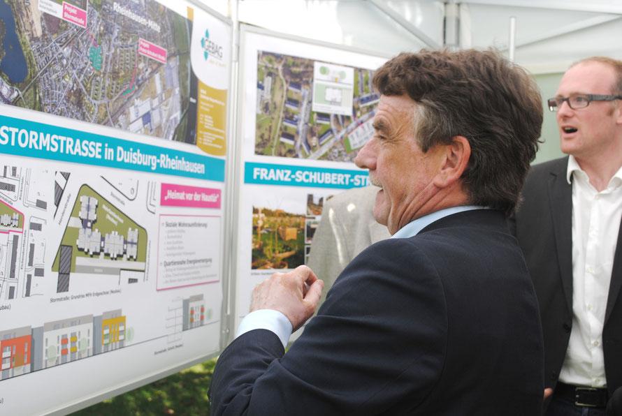 NRW Wohnungs- und Städtebauminister Michael Groschek und der Oberbürgermeister der Stadt Duisburg Sören Link bestaunen die Neubaupläne der GEBAG für die Franz-Schubert-Straße in Duisburg-Rheinhausen.