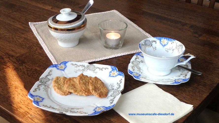 Ein seltenes Gedeck mit eckigem Teller und Untertasse; auf dem Teller: kleine Haferkekse