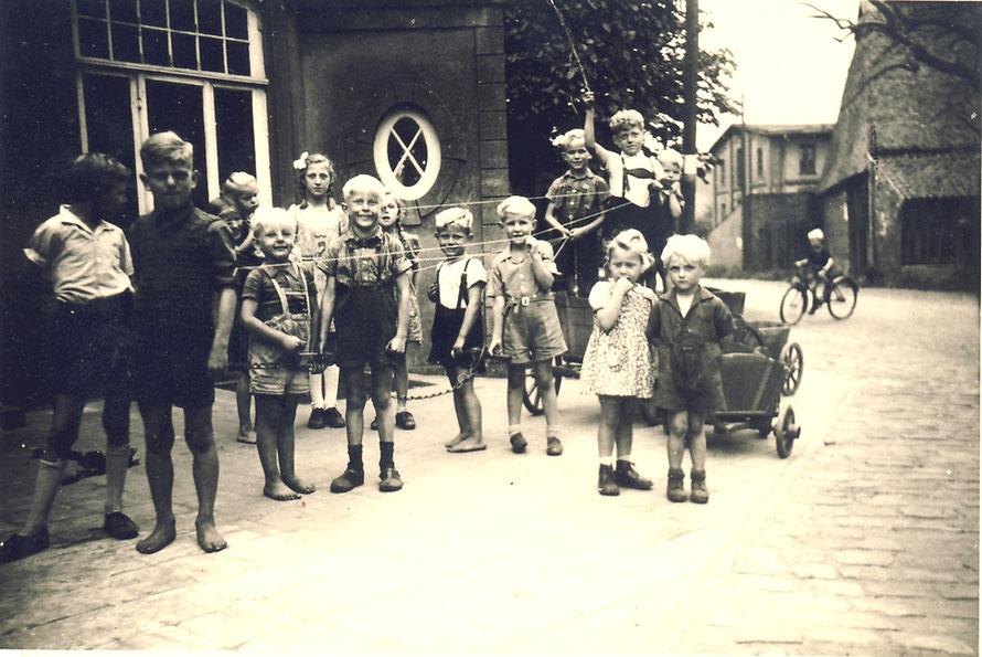 1952: Kinder vor der Bäckerei Koldeweyh auf der Dorfstraße. Im Hintergrund der Hof Budelmann mit der Motormühle.13