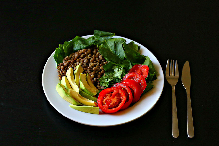 Lentils with avocado salad bowl on a plate black background