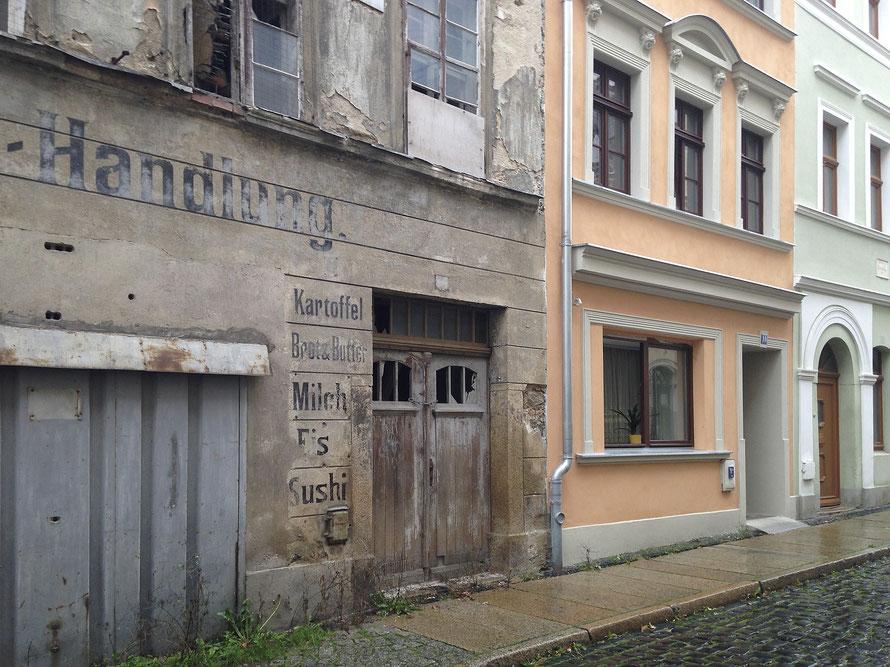 """Die ehemalige Feinkosthandlung in der Krischlstraße in Görlitz. Der Schriftzug """"Sushi"""" ist eine Intervention im öffentlichen Raum von Isabelle Enders ergänzt."""