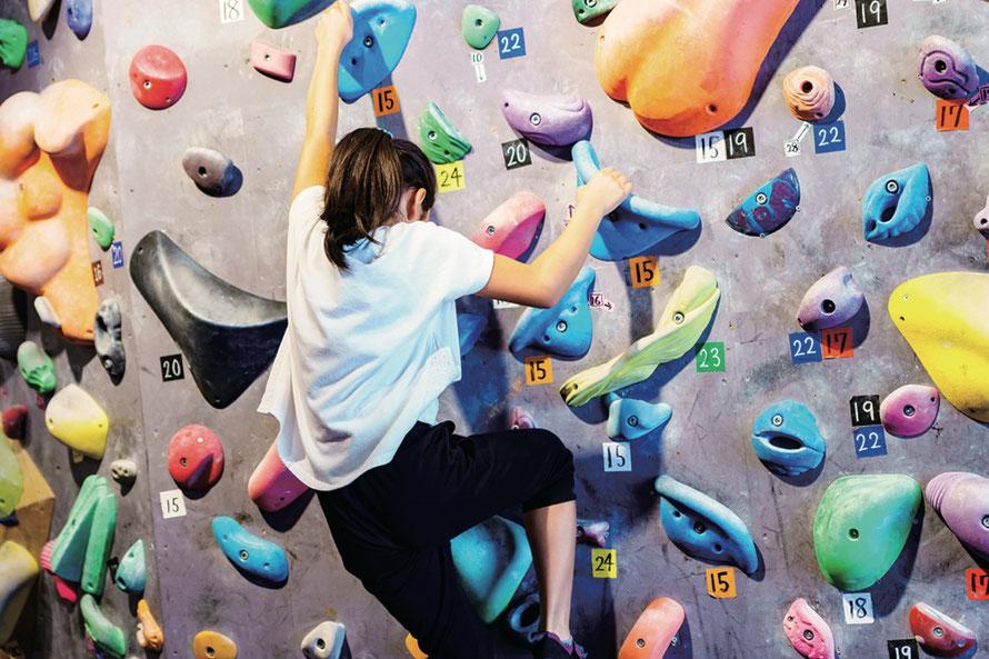 [写真]中学生の女の子が自力でボルダリングに挑戦している様子