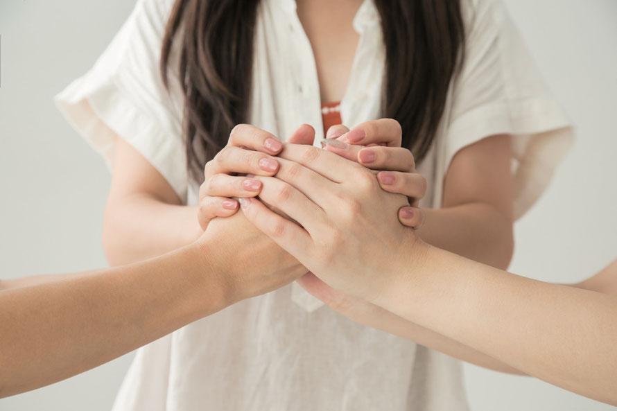 [写真]女性が二人の人物の手を握り寄せている様子