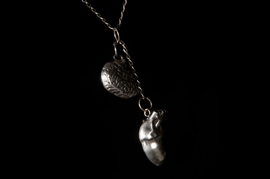 Con Razón, Corazón. silver. works like a scale where the heart will always pull down as it is heavier.