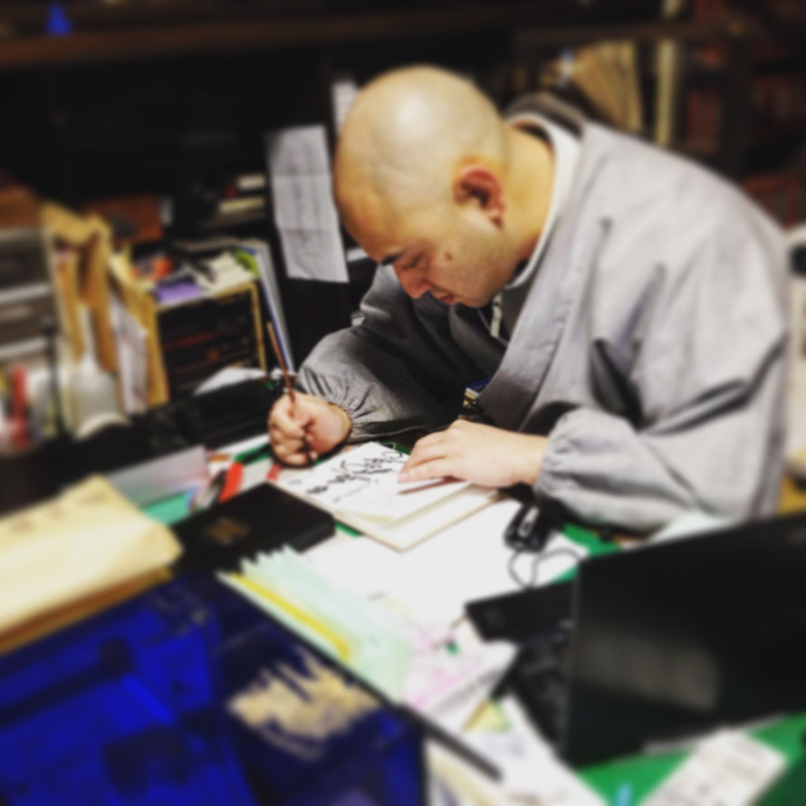 Monje escribiendo/dibujando una caligrafía en un libro de caligrafías de templos.  Se pagan 100 o 200 yenes y lo hacen en estos libros en blanco que los peregrinos y turistas llevamos en nuestros periplos templarios.