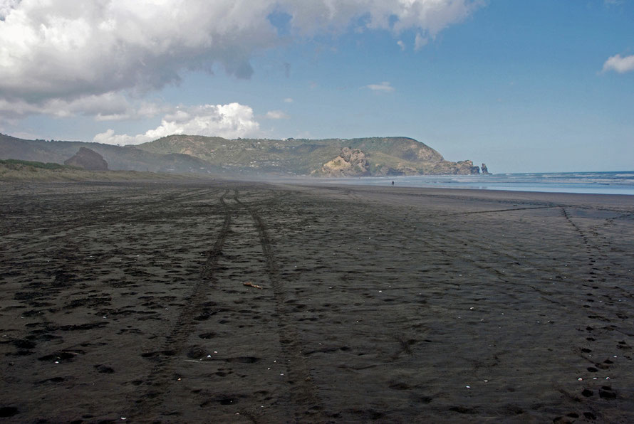 The vastness of Piha Beach at low tide from the north end, the Lion Rock on the left and the scruffy, pillowy blak sand stretching away to Taitomo Island and the Nun Rock.