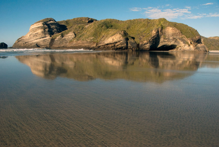Brilliant reflections at Wharariki Beach in the film of seawater overlying the tidal sands.