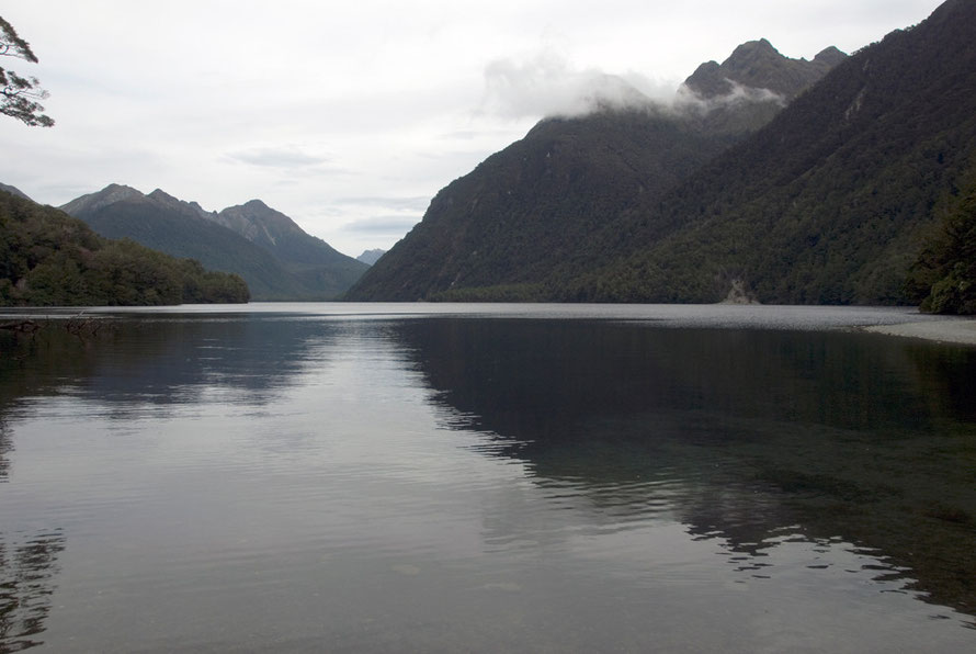 The inky waters of Lake Gunn (480m) on the Milford Road looking south to Melita Peak. Highway 94 snakes through the beech forest on the left hand side of the lake.