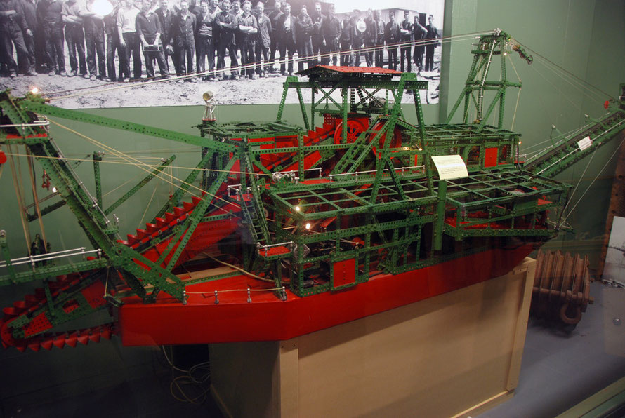 The giant Meccano model of Gold Dredger built by Blake Huffam with a photo of the workers who used to run the real-life dredger (Hokitika Museum)