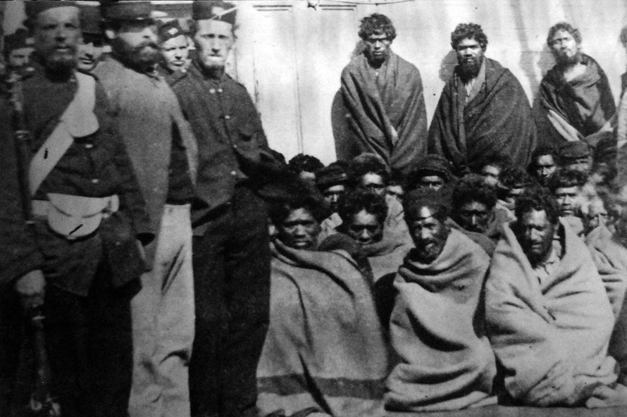 Maori prisoners, members of the Hauhau church, under guard on board a prison hulk in Wellington Harbour, 1866. The prisoners were captured at Wereroa Pa, Waitotara, 20 miles north of Wanganui.