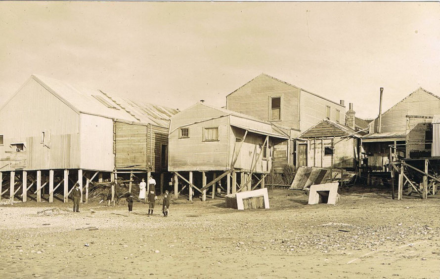 The undercut buildings of Revell Street in 1914 after sea flooding (click for link at postcard.org.nz